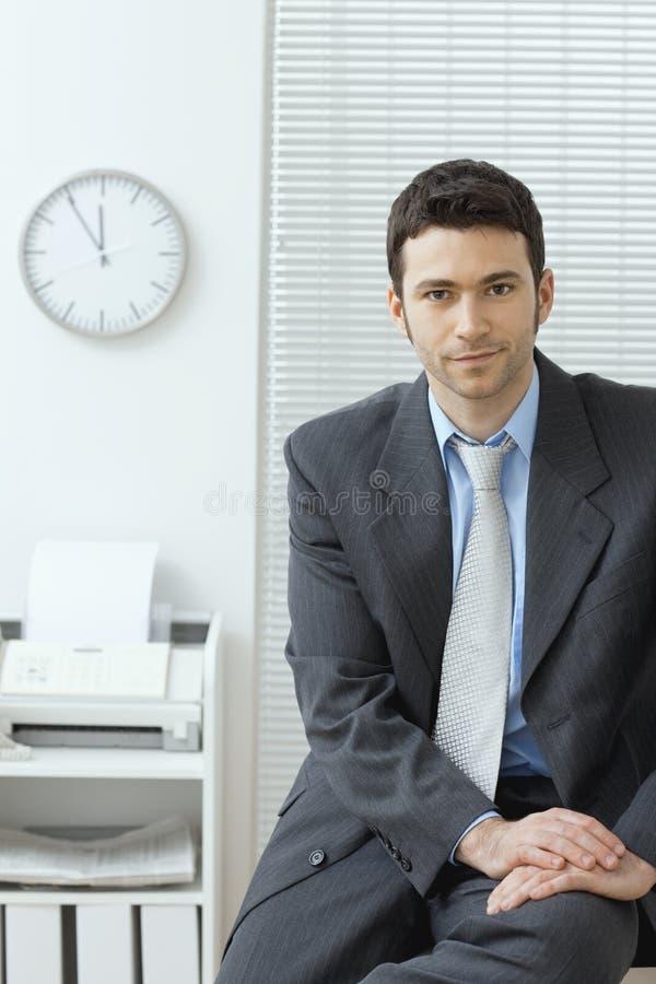 Geschäftsmann, der auf Schreibtisch sitzt stockfotografie