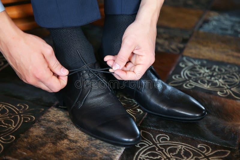 Geschäftsmann, der auf schwarze Lederschuhe für Arbeit sich setzt stockfotos