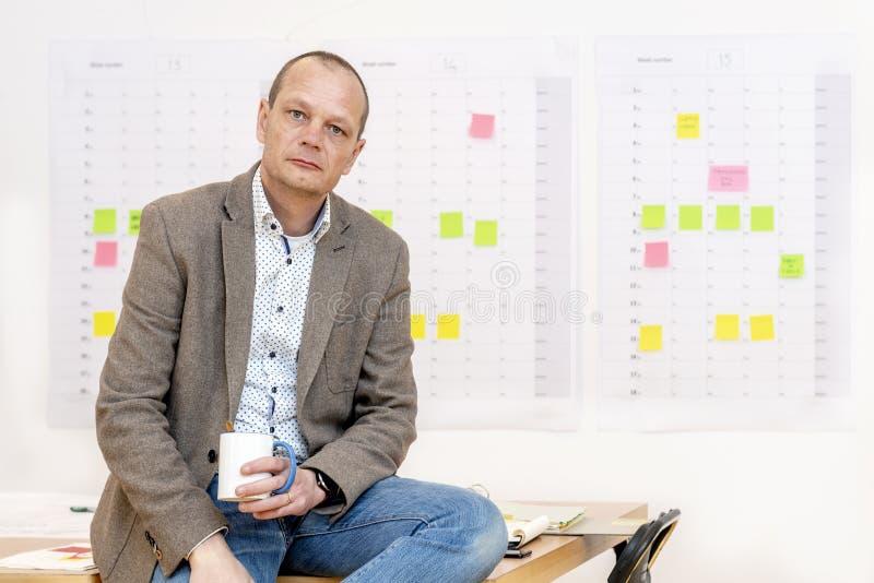 Geschäftsmann, der auf seinem Schreibtisch sitzt stockfotos