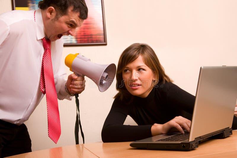 Geschäftsmann, der auf seinem Teilnehmer im Büro kreischt stockbilder
