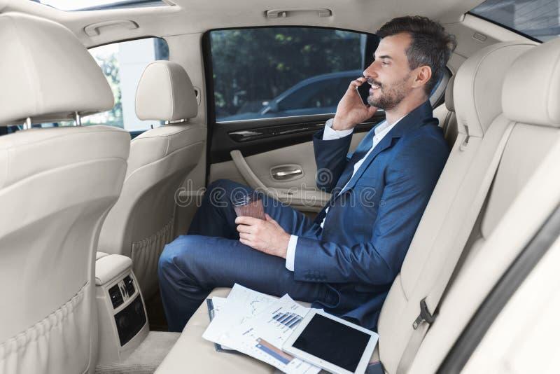 Geschäftsmann, der auf Smartphone und trinkendem Kaffee spricht lizenzfreies stockfoto