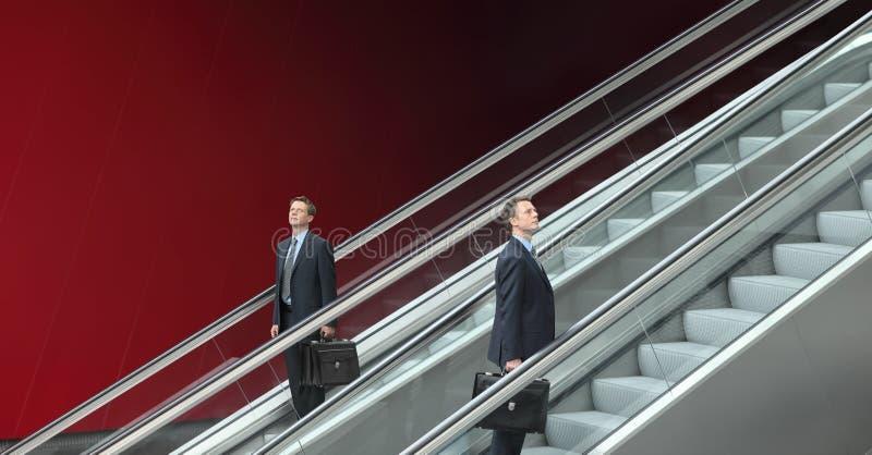 Geschäftsmann, der auf und ab Rolltreppen, Konzept des Erfolgs geht lizenzfreies stockfoto