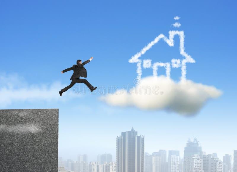 Geschäftsmann, der auf Wolkentraumhaus läuft und springt stockfoto