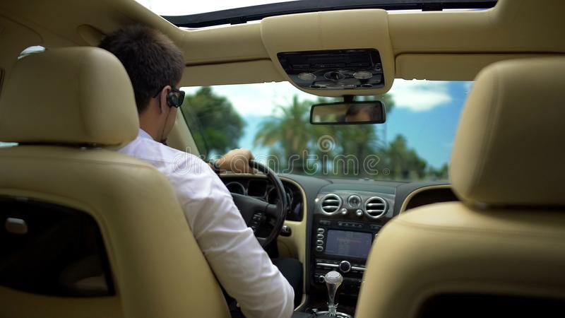 Geschäftsmann, der Auto fährt und am Telefon über drahtlosem Kopfhörer, Technologie spricht stockbilder