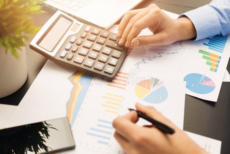 Geschäftsmann, der an Börsediagrammen und -diagrammen arbeitet stockfotos