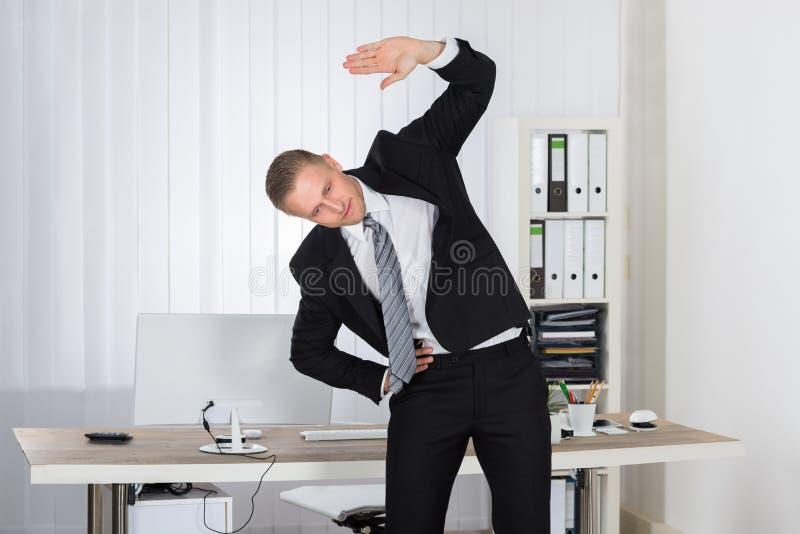 Geschäftsmann, der in Büro ausdehnt lizenzfreie stockbilder