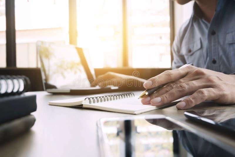 Geschäftsmann, der am Büro mit Laptop und an den Dokumenten auf seinem Schreibtischfreiberuflerkonzept arbeitet stockbilder