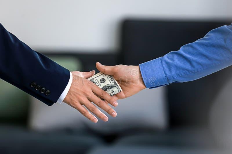 Geschäftsmann, der Bestechungsgeld vom Mann nimmt Dollarbanknoten im Umschlag getrennt auf Wei? lizenzfreie stockbilder