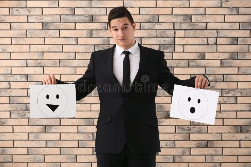 Geschäftsmann, der Blätter Papier mit gezogenen Emoticons gegen Backsteinmauer hält lizenzfreie stockfotos