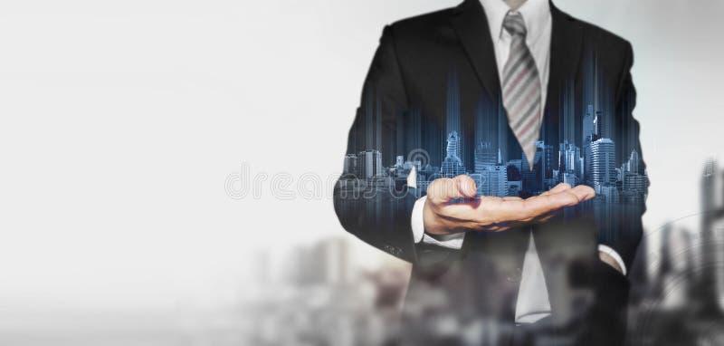 Geschäftsmann, der blaues Hologramm von modernen Gebäuden, mit Unschärfehintergrund und Kopienraum hält lizenzfreies stockbild
