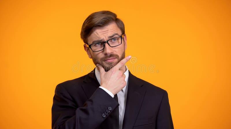 Gesch?ftsmann, der das Kinn denkt ?ber Startstrategie, orange Hintergrund verkratzt stockfotografie