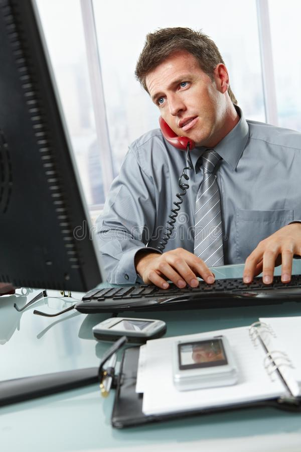 Geschäftsmann, der das Schreiben im Büro benennt stockfotografie