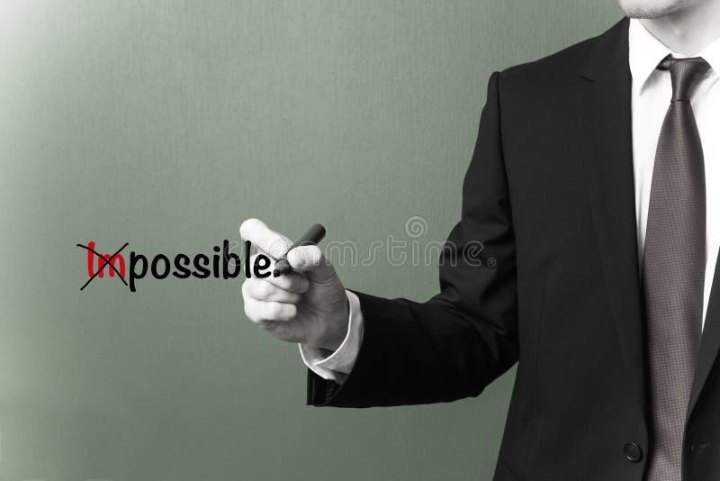 Geschäftsmann, der das Wort unmöglich in mögliches ändert stockfoto