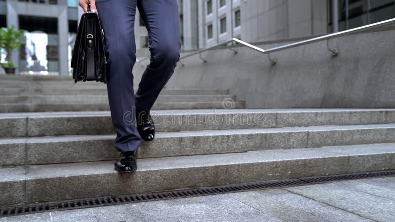 Geschäftsmann, der den Aktenkoffer geht, gehend zur wichtigen Sitzung unten, halten stockfotografie
