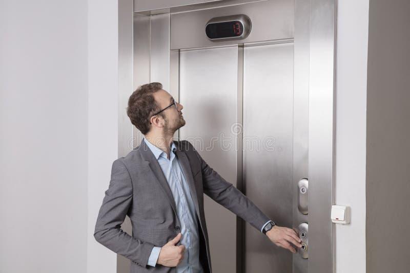 Geschäftsmann, der den Aufzug nennt lizenzfreies stockbild