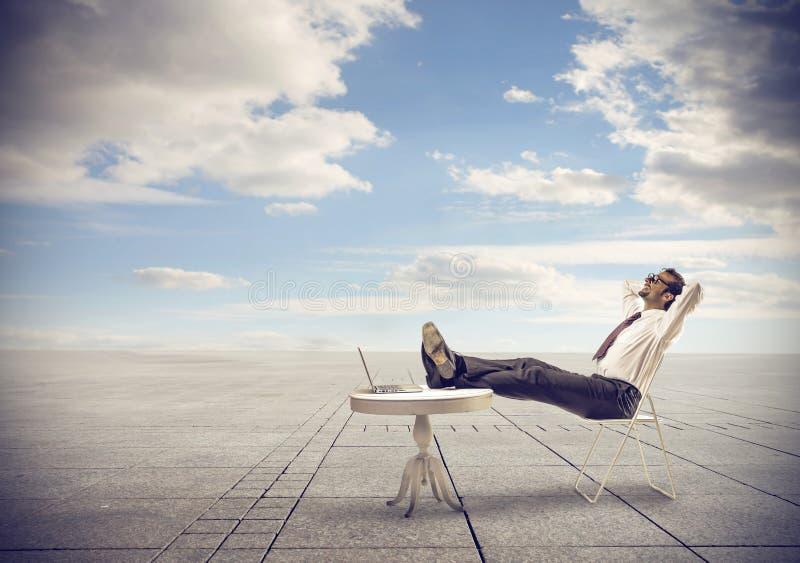 Geschäftsmann, der den Himmel betrachtend sich entspannt stockfoto