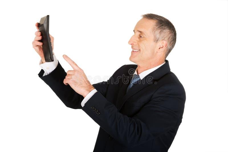 Geschäftsmann, der den Knopf auf Taschenrechner betätigt stockbild