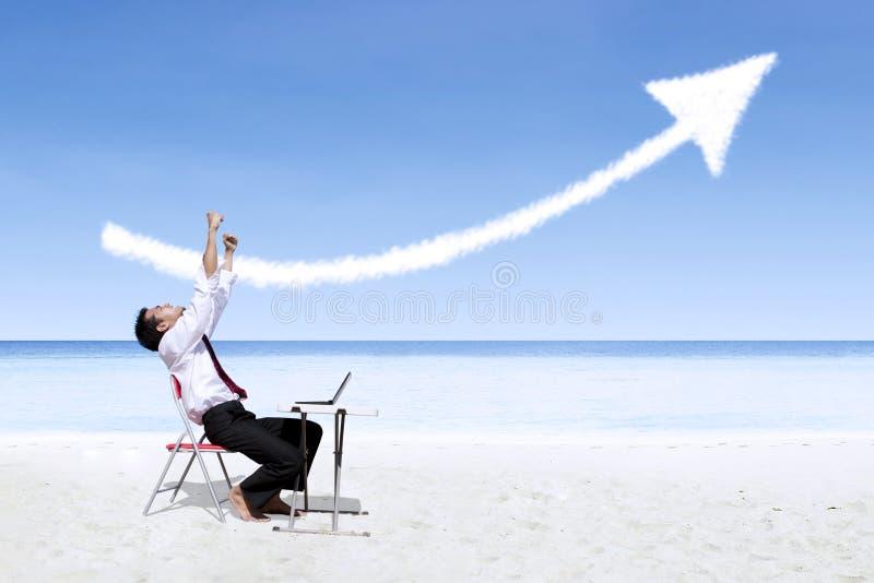 Geschäftsmann, der in der Freude betrachtet Erfolgspfeilzeichen auf Strand lacht stockfoto