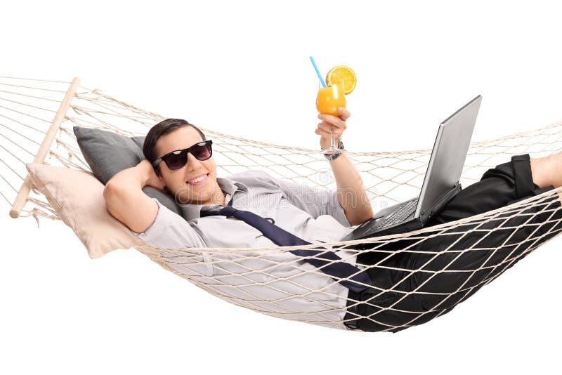 Geschäftsmann, der in der Hängematte liegt und ein Cocktail trinkt stockfoto