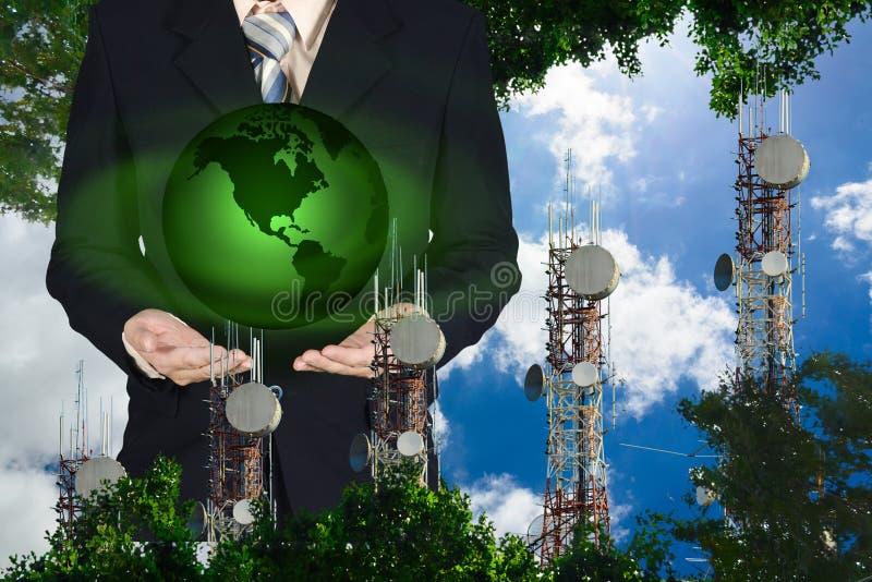 Geschäftsmann, der in der Hand den grüne Erdplaneten steht auf Hintergrund des blauen Himmels und der Wolke mit Telekommunikation lizenzfreie stockfotografie