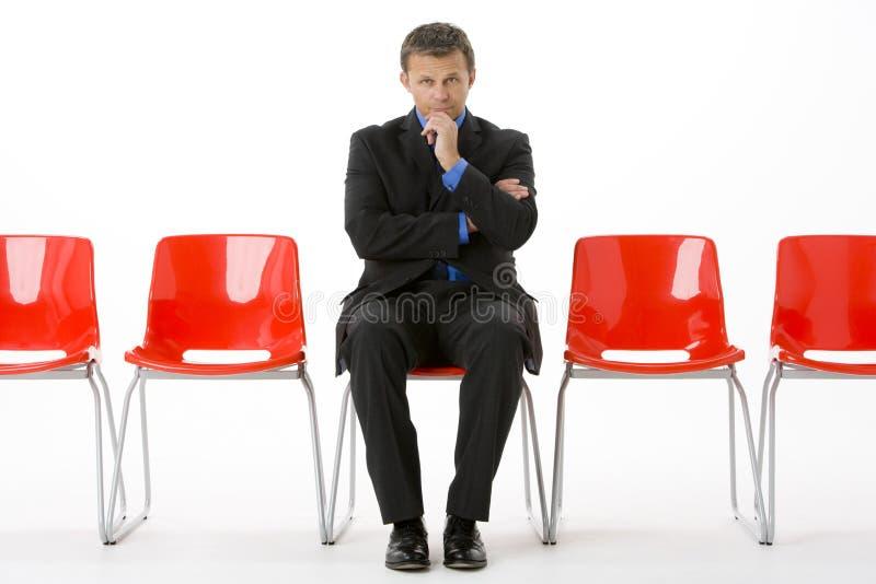 Geschäftsmann, der in der Reihe der leeren Stühle sitzt stockfoto