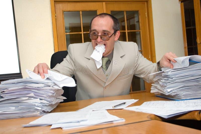 Geschäftsmann, der die Arbeit isst lizenzfreie stockfotografie