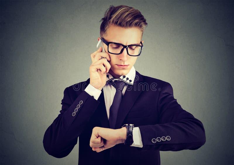 Geschäftsmann, der die Armbanduhr, sprechend am Handy betrachtet lizenzfreie stockfotos