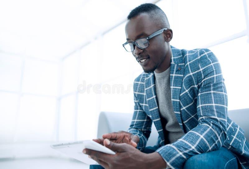 Geschäftsmann, der die digitale Tablette sitzt im Bürowarteraum verwendet lizenzfreie stockfotografie