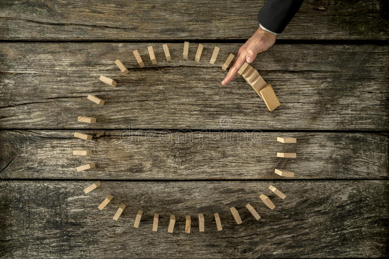 Geschäftsmann, der die fallenden Dominos gelegt in einen Kreis mit seinem stoppt lizenzfreies stockbild
