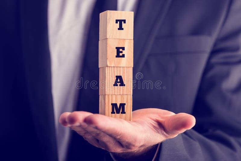 Geschäftsmann, der die hölzernen lesenden Würfel - Team hält stockbild