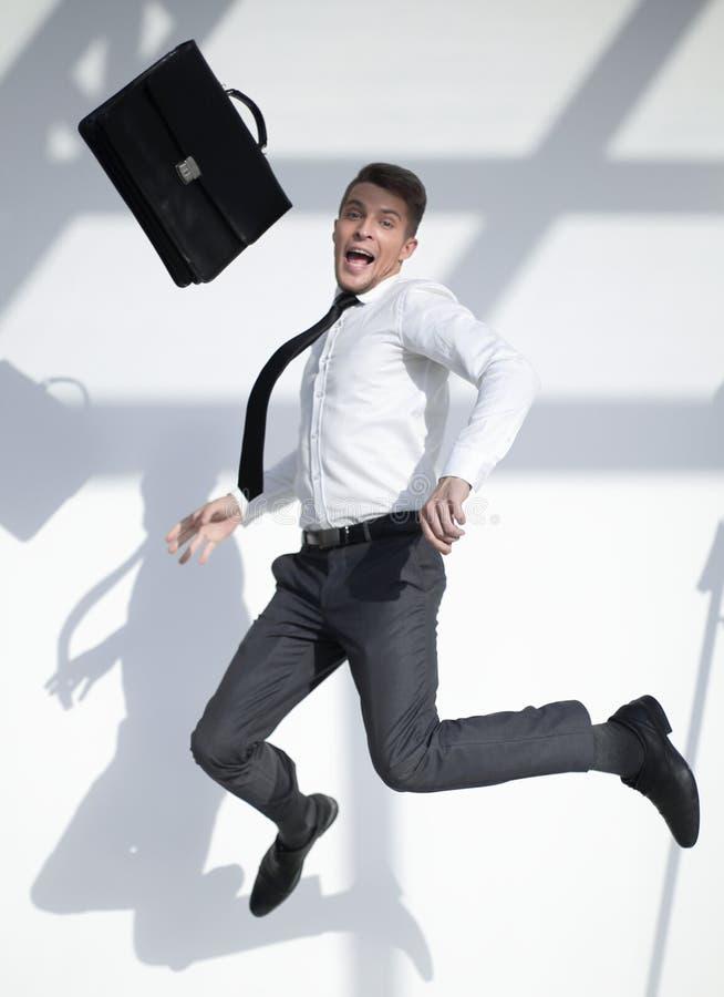Geschäftsmann, der in die Luft mit einem großen Lächeln auf seinem Gesicht springt lizenzfreies stockbild
