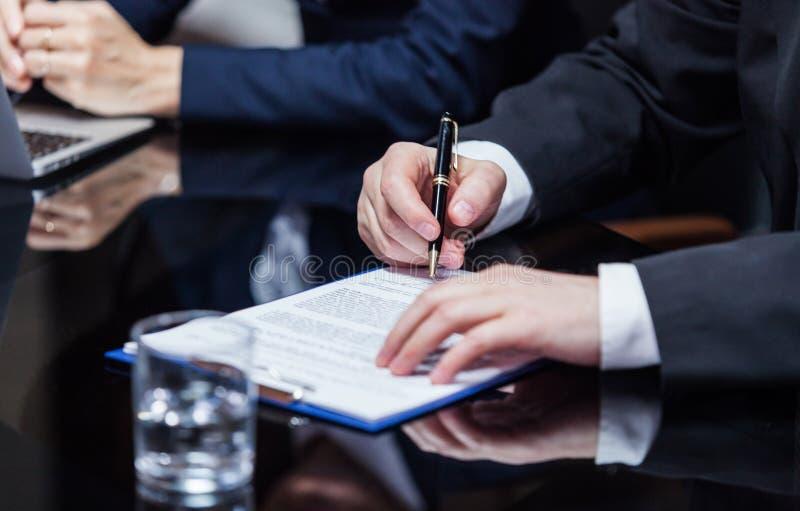 Geschäftsmann, der die Papiere unterzeichnet stockbild