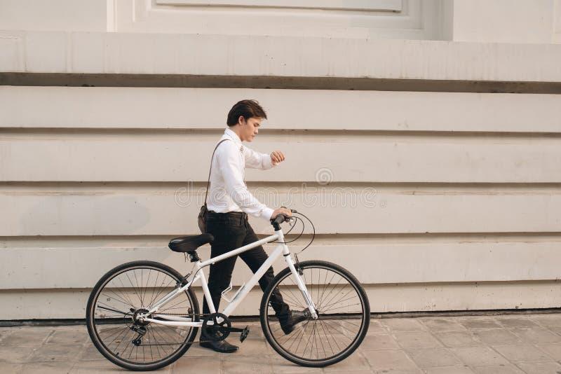 Geschäftsmann, der die Zeit beim Austauschen auf seinem Fahrrad überprüft lizenzfreie stockfotos