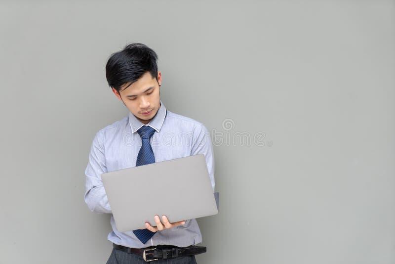 Geschäftsmann, der digitale Laptop-Computer auf Hintergrund mit c hält stockbild