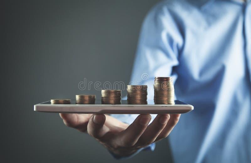 Geschäftsmann, der digitale Tablette mit Münzen hält Die goldene Taste oder Erreichen für den Himmel zum Eigenheimbesitze stockbilder