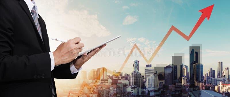 Geschäftsmann, der an digitaler Tablette, mit Panoramastadtansicht arbeitet und oben das Diagramm und Pfeil, Geschäftswachstum da stockbild