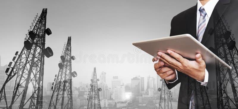Geschäftsmann, der an digitaler Tablette, mit panoramischen Stadtbild- und Telekommunikationstürmen der Doppelbelichtung arbeitet stockfoto