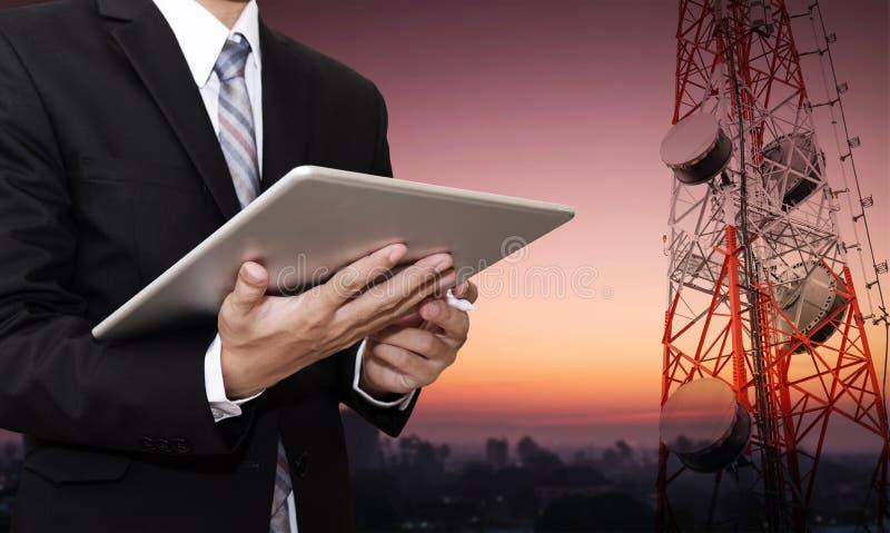 Geschäftsmann, der an digitaler Tablette, mit Satellitenschüsseltelekommunikationsnetz auf Telekommunikationsturm an der Landscha lizenzfreie stockbilder