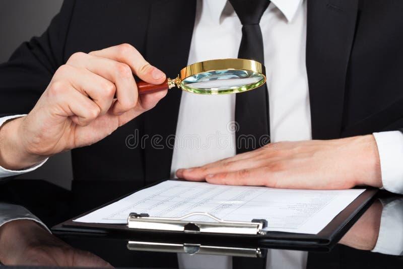 Geschäftsmann, der Dokument mit Lupe am Schreibtisch analysiert stockfotografie