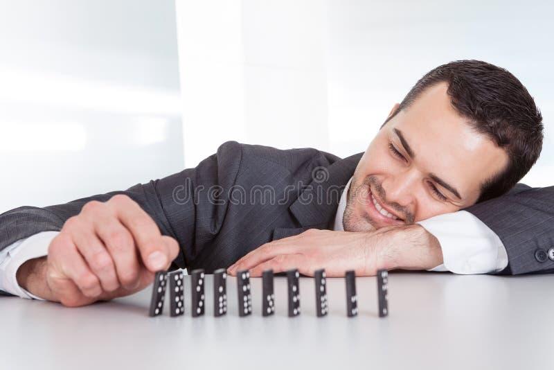Geschäftsmann, der Domino spielt stockfotografie