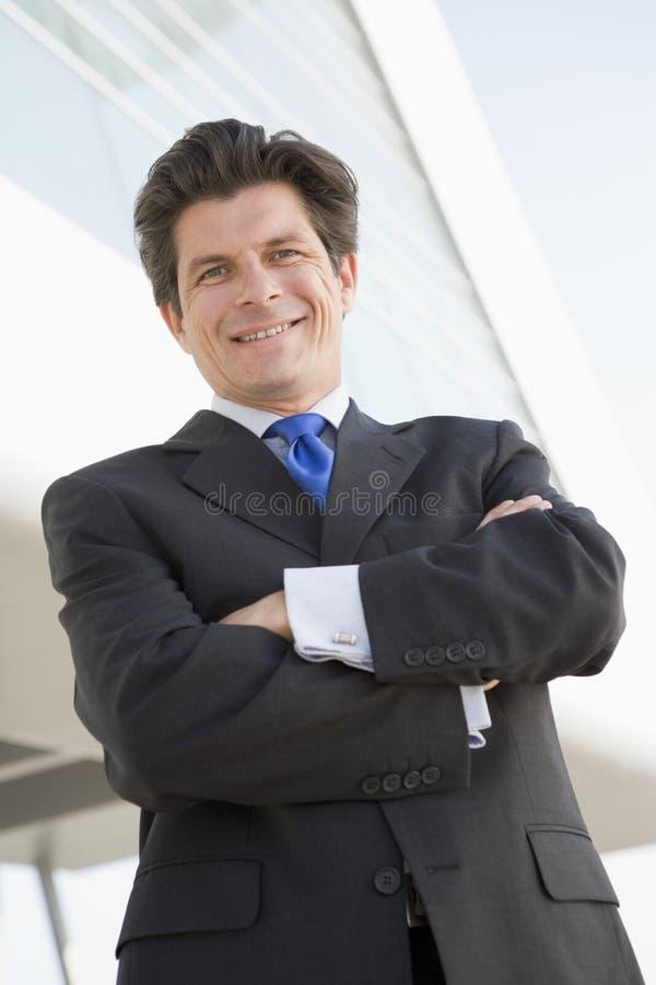 Geschäftsmann, der draußen durch das aufbauende Lächeln steht lizenzfreie stockfotos