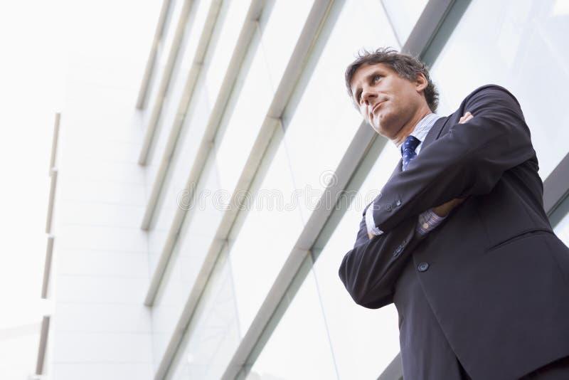 Geschäftsmann, der draußen durch Gebäude steht stockfotos