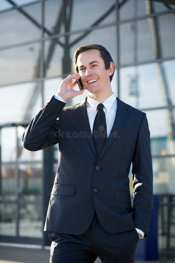 Geschäftsmann, der draußen durch Handy lächelt und nennt lizenzfreies stockbild