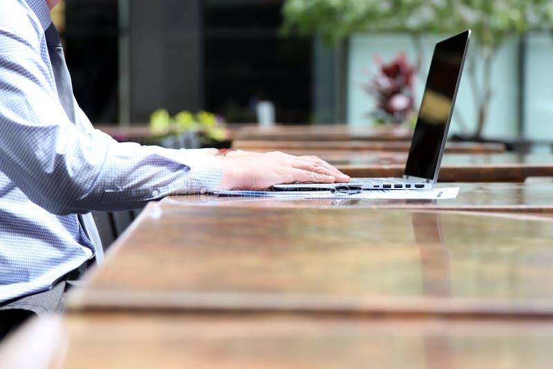 Geschäftsmann, der draußen Finanzzahlen auf Diagramme auf einem Laptop bearbeitet und analysiert stockfotografie