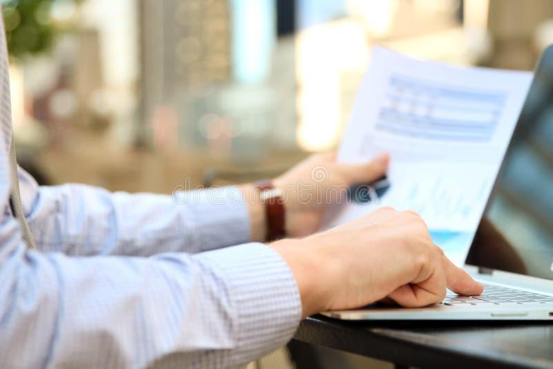 Geschäftsmann, der draußen Finanzzahlen auf Diagramme auf einem Laptop bearbeitet und analysiert lizenzfreies stockbild