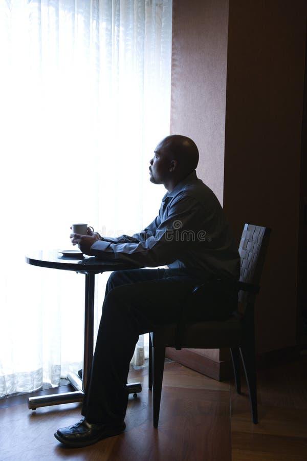 Geschäftsmann, der durch Cafe Window sitzt stockfotos