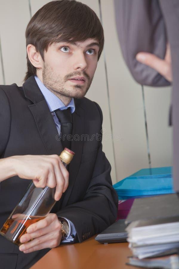 Geschäftsmann, der durch die Arbeit trinkt lizenzfreies stockbild