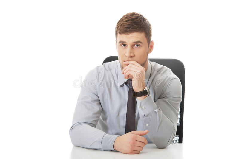Geschäftsmann, der durch einen Schreibtisch im Büro sitzt lizenzfreie stockbilder