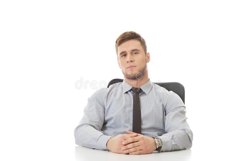 Geschäftsmann, der durch einen Schreibtisch im Büro sitzt lizenzfreie stockfotografie