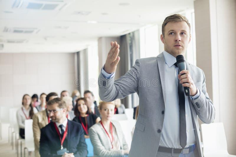 Geschäftsmann, der durch Mikrofon während des Seminars in Konferenzzentrum spricht stockfoto